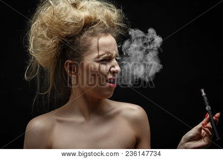 Young Woman Smoking Electronic Cigarette On Black Background, Grimacing, Cough