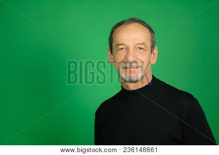 Male Face Of Senior Man With Well-trimmed Beard And Gray Hair On A Green Background In Studio.