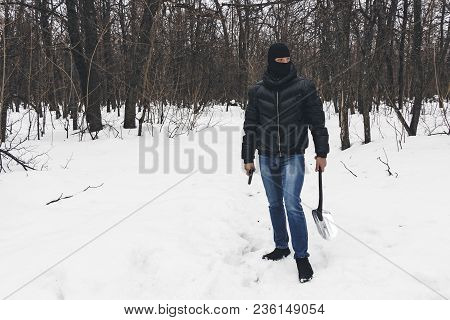 Murderer In The Black Mask With Gun And Shovel Leaves Place Of The Crime, Going Through The Snow In