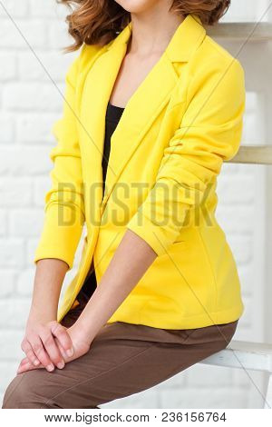 Beautiful Woman Dressed In Yellow Jacket Over Background. Closed Arms Of A Girl In A Bright Yellow J