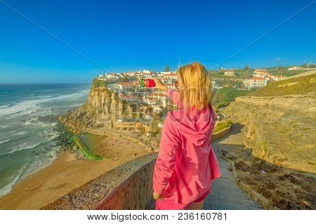 Blonde Woman Takes Photo Of Azenhas Do Mar On Atlantic Ocean. Female Tourist Takes Pictures By Mobil