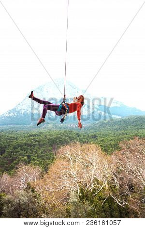 A Woman Is Hanging On A Rope In The Background Of Beautiful Mountains. The Climber Goes Down. The Gi