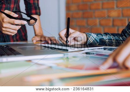 Co-worker Working With Graphic Design In Office Room Together.