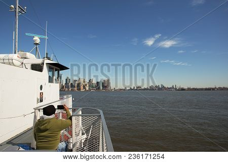 Ellis Island Ferry, New York - Feb 28, 2018:  A Tourist Snaps A Photo Of The Manhattan Skyline From