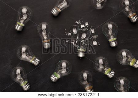 One Broken Light Bulb Among Whole Ones On Black Background, Top View. Creativity And Fragility Conce