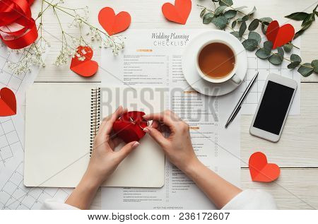 Wedding Background With Checklist And Calendar. Female Hands Holding Rings In Red Box And Arranging