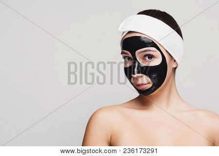 Skin Care. Portrait Of Young Girl With Black Mask On Face. Purifying Spa Treatment, White Studio Bac