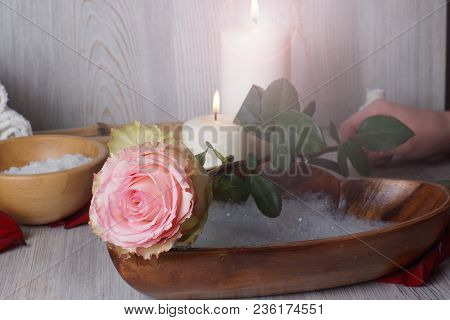 A Female Hand Puts A Rose, A Preparation For A Spa Procedure For The Skin Of The Hands