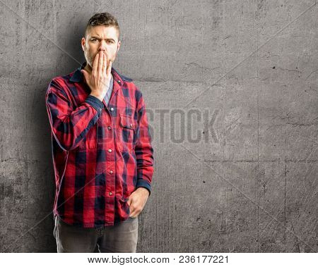 Young handsome man covers mouth in shock, looks shy, expressing silence and mistake concepts, scared