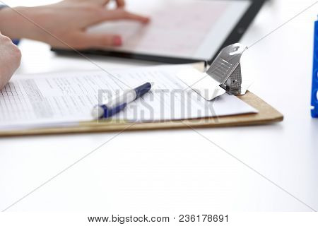 Woman Doctor Using Tablet Computer While Sitting At The Desk In Hospital Closeup. Cardiologist Check
