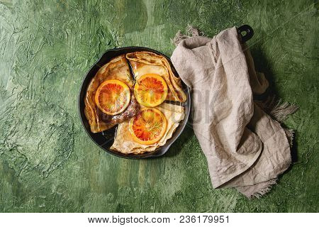 Homemade Crepes Pancakes Served In Cast-iron Pan With Bloody Oranges And Rosemary Syrup With Sliced