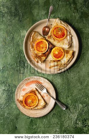 Homemade Crepes Pancakes Served In Ceramic Plates With Bloody Oranges And Rosemary Syrup With Sliced