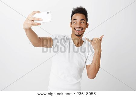 Studio Shot Of Positive Good-looking African-american Male With Afro Hairstyle Holding Smartphone An
