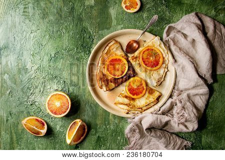 Homemade Crepes Pancakes Served In Ceramic Plate With Bloody Oranges And Rosemary Syrup With Sliced