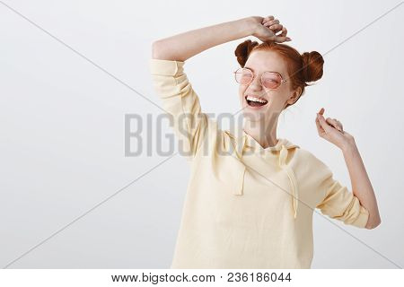 Good-looking Feminine Redhead Girlfriend In Stylish Outfit And Sunglasses Raising Hands While Dancin