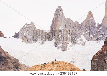 Far Away Abstract View To Fitz Roy Mountain Range With Tiny People And Tourists Walking In The Surro