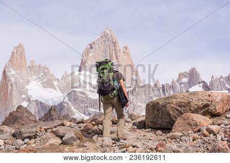 Young Man Walking Up To Mount Fitz Roy With A Backpack With Effort On A Clear Sunny Summer Day, Near