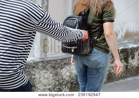 Thief In Black And White Jacket Stealing The Wallet Or Mobile Phone From Behind Young Caucasian Woma