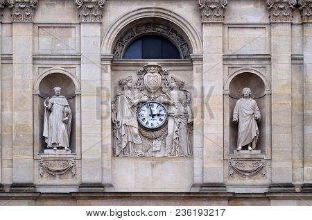 PARIS, FRANCE - JANUARY 05,2018: St. Thomas Aquinas, Pierre Lombard, muses support the clock, topped by the coat of arms of Cardinal Richelieu, facade of the St Ursule chapel of the Sorbonne in Paris.