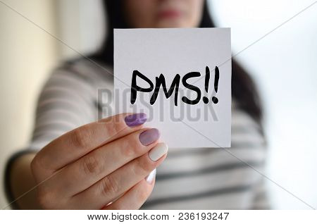 Young Sad Girl Shows A White Sticker. Caucasian Brunette Holding A Sheet Of Paper With Message. Pms