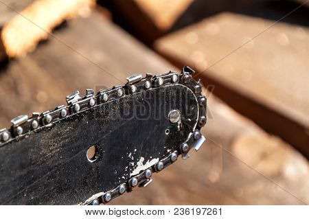 Closeup View Of A Chainsaw Bar And Cutting Chain. Dirty Blade Of A Chainsaw. Blade Of A Chainsaw In