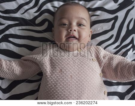 Portrait Of A 4 Months Old Baby Girl Lying On Back On Parents Bed Laughing
