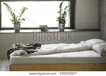Unmade Messy Double Bed For Two With Crumpled Bedding Sheet Linen Near Window In Modern Comfortable