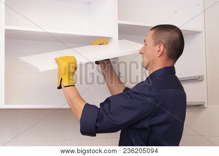 Worker Assembles Furniture In The Kitchen