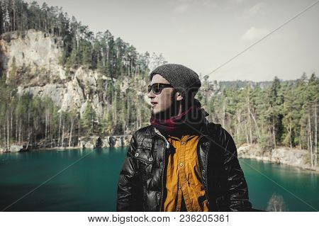 Young Hister Boy In Sunglasses And Jaket With Shirt Near A Lake