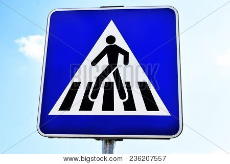 Pedestrian Crossing Road Sign On Blue Cloudy Spring Sky Background.