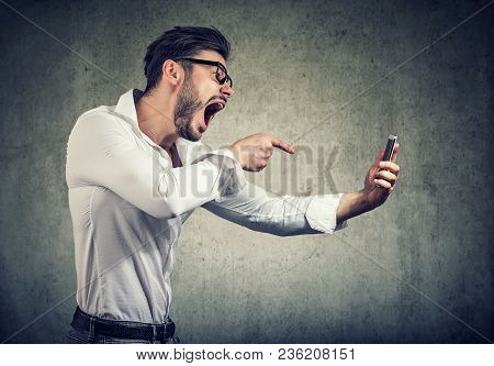Side View Of Bearded Man In Glasses Holding Smartphone And Yelling At It Being Rude.
