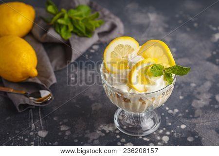 Lemon dessert, lemon trifle, cheesecake, whipped cream, parfait. Fruit mousse in glass on a dark background. poster