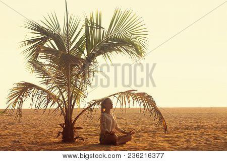 A Woman Meditating Under A Palm Tree