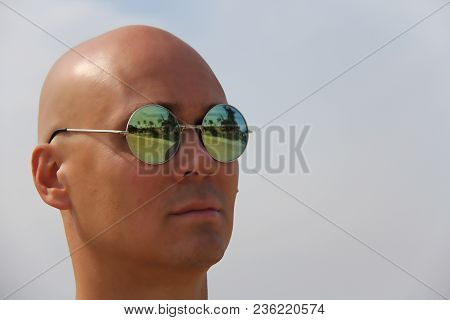 Bald Man In Mirror Sunglasses. A Beautiful Tanned Man On Vacation. Portrait Of A Man Close-up. Palm