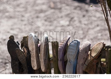 Picture Of Poverty In Old Worn House Slippers On Wooden Fence. Space For Text