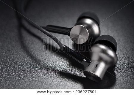 Metallic Ear Buds Or Earphones On Dark Black Background