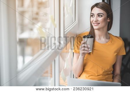 Portrait Of Good Looking Girl Relaxing On Windowsill With Cup Of Beverage In Hand. She Is Smiling. C