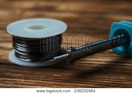 Soldering Iron And Solder Wire On Wooden Table Background, Close-up