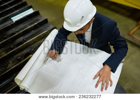 High Angle View Of Concentrated Young Engineer Wearing Protective Helmet And Hardhat Making Necessar