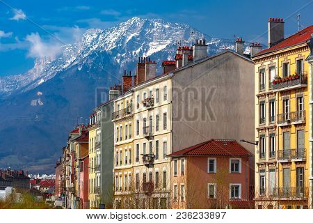 Typical French Houses With Tiled Roofs And Chimney Pipes Against The Backdrop Of The Alps, Grenoble,
