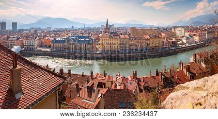 Scenic Panoramic Aerial View Of The Banks Of The Isere River, Bridge, And Old Town With French Alps