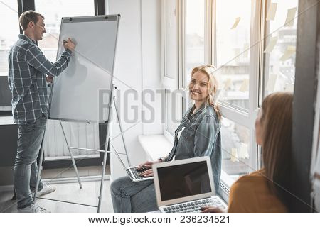 Smiling Man And Women Working In Office. Guy Writing On Whiteboard And His Female Colleagues Using N