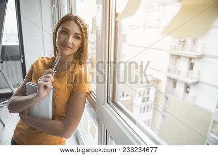 Portrait Of Pensive Woman With Sketchbook In Arms. She Is Reclining On Window In Her Office. Copy Sp