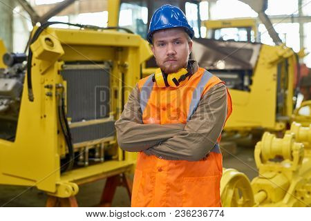 Waist-up Portrait Of Bearded Technician Wearing Reflective Vest And Hardhat Posing For Photography W
