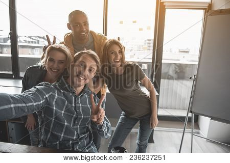 Portrait Of Four Happy People Making Snapshot Of Themselves At Work. They Are Showing Peace Sign Tak