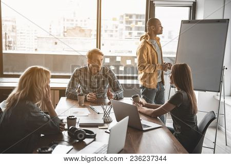 Calm Man Standing Near Whiteboard While His Partners Sitting At The Table With Coffee Cups And Conve