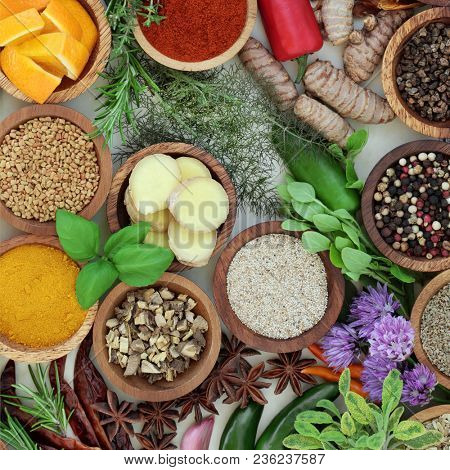 Spice and herb selection  in wooden bowls and loose forming an abstract background. Top view.