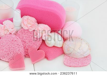 Bathroom and health spa beauty cleansing products with carnation flowers, heart shaped soaps, bath bomb, body lotion, sponges, wash cloths and seashells on white wood background.