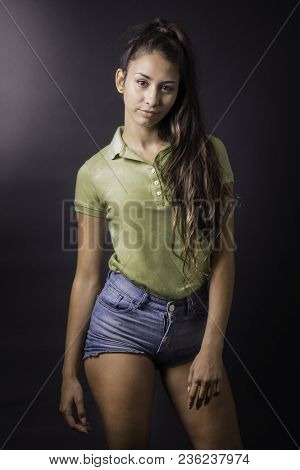 Portrait Of Young Beautiful Latin Woman In Front Of A Dark Background
