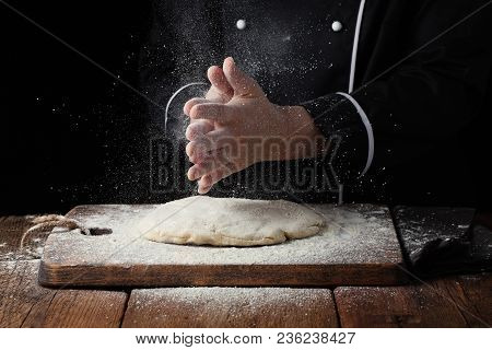 Woman Chef Hand Clap With Splash Of White Flour On A Black Background.